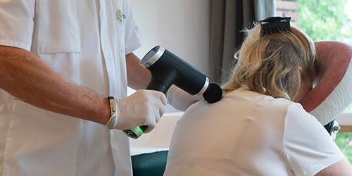 Masseur Bonky Nooij, behandeling met massagepistool.
